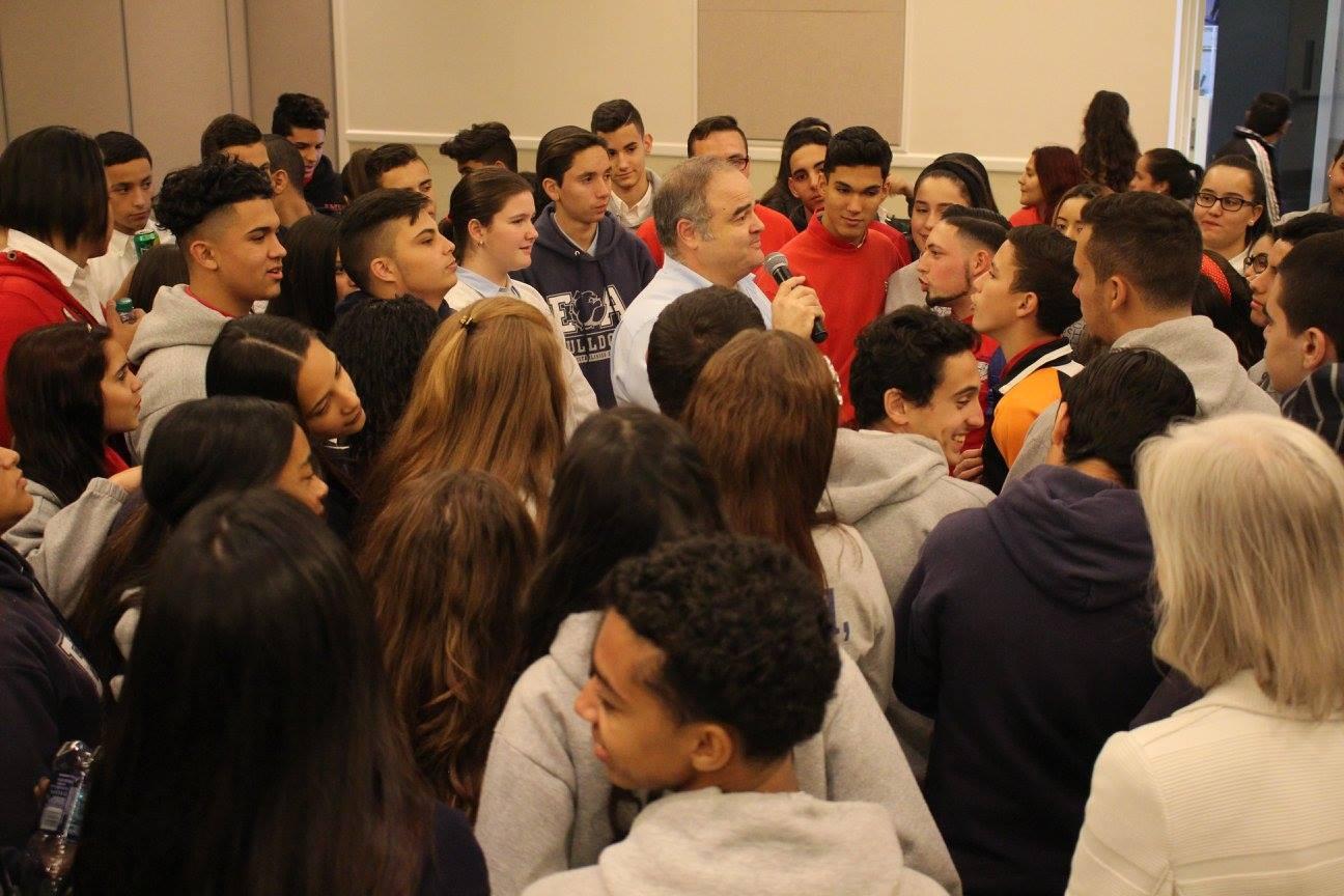 El artista Xavier Cortada (al centro con el micrófono) habla a los estudiantes acerca del desarrollo del arte sobre el cambio climático