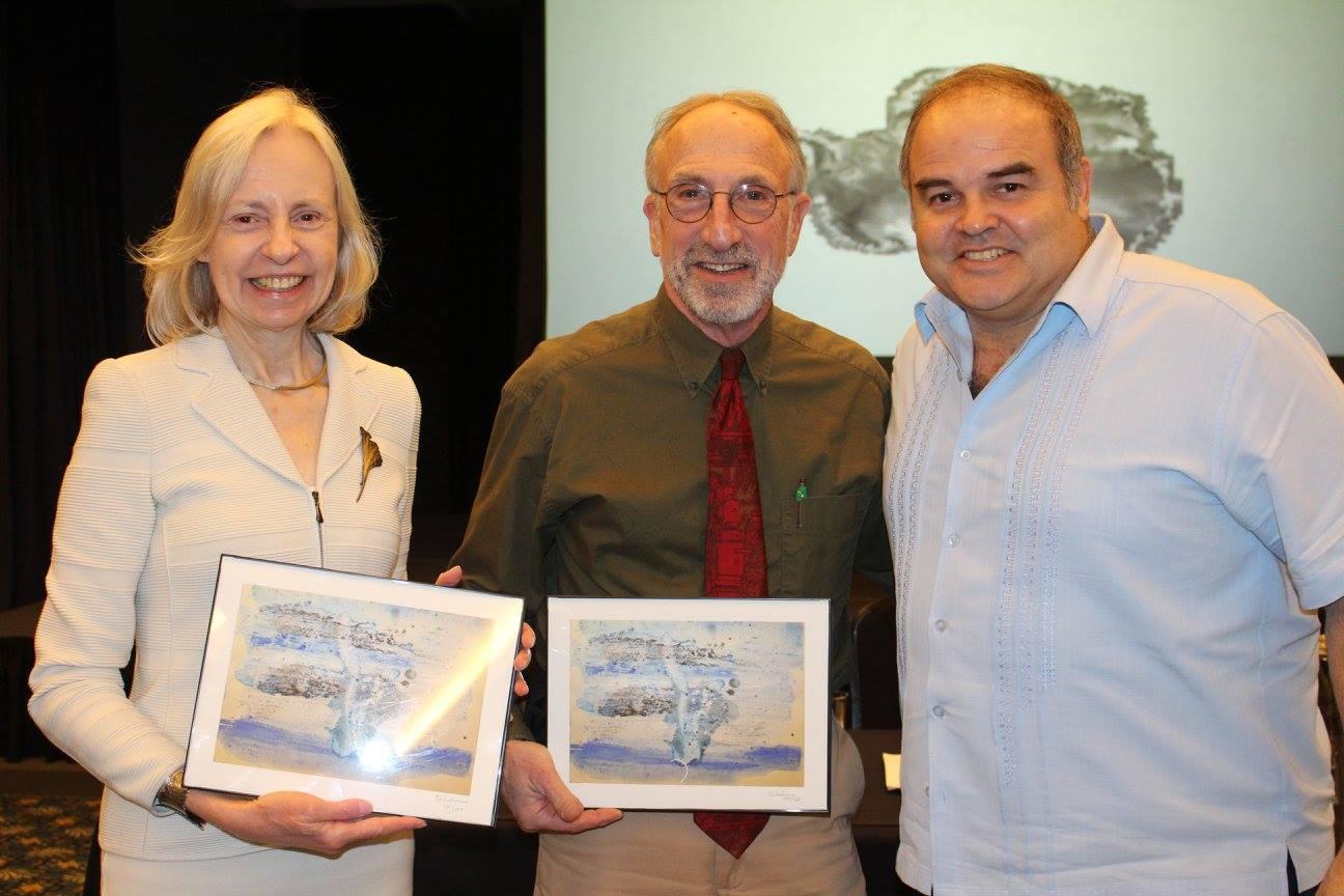 El artista Xavier Cortada (derecha) presenta a la Directora de Honoring the Future, Fran Dubrowski (izquierda) y al Asesor Artístico Peter Handler (centro), impresiones de la acuarela que Cortada realizó usando sedimentos y hielo Antártico.